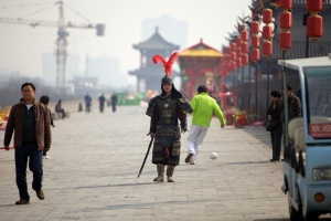 A dressed up warrior walking along the Xi'an city wall. A wall with hundreds of years of history, standlng solidly in this changing world. Despite an actor, he contributes to this photo with a contrast of modern and history.