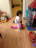 While Ashton was pushing his scooter, Annabelle tried to ride on it!