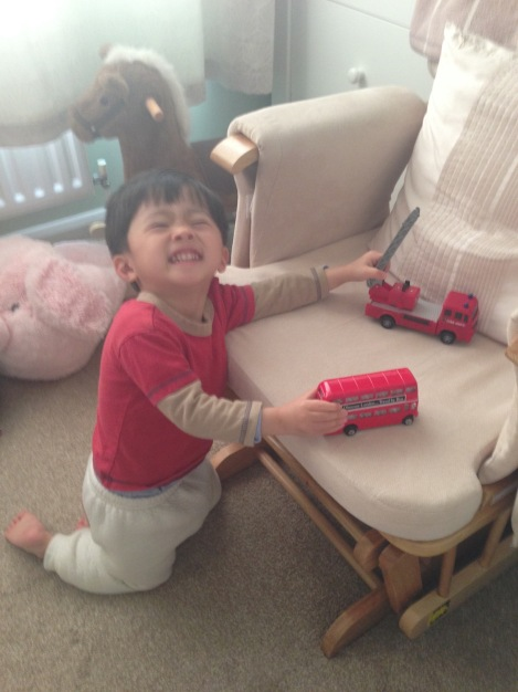 Morning exercise, pushing his toy buses and fire engine.