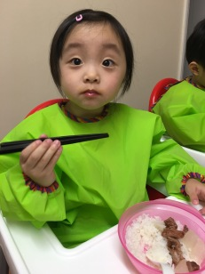 Annabelle learns to use chopsticks.